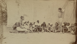 A private teacher in one of the indigenous schools in Varanasi (Benares) teaching boys to write letters and figures on the ground. The standing boy with arms raised is undergoing punishment